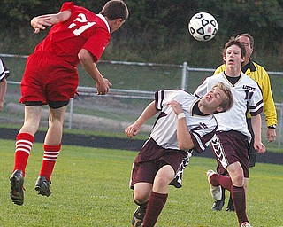 LIBERTY - LABRAE - (21) Jacob Jaros and (8) Pat McGarry play the ball as (11) Eric Wolf looks on during their game Wednesday night at Liberty.