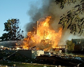 A neighboring residence caught fire after a house on the corner of Townsend and Washington Streets in Girard exploded Thursday, July 18, 2008. Photo by James Hughes.