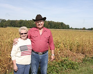 Linda and Henry Lipps stand next to where a GMA truck backed into their soybean field. Behind them by the trees is the railroad track where GMA officials unloaded to meet Linda and Henry.