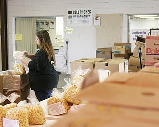 Cathy Headley of Struthers is the Repack Coordinator at Second Harvest Food Bank. Seen here, she is packing 1lb bags full of cereal.