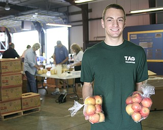 Cory Kranek (age 15) of Boardman is holding bagged apples at Second Harvest Food Bank on Saturday where he volunteered and packed food bags.