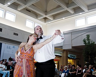 FEELING THE MUSIC: Davine George, left, of Youngstown dances the waltz with dance partner Dean Wellendorf of Canfield. The ballroom dancing exposition took place in the main concourse area of Eastwood Mall on Saturday afternoon. Dance enthusiasts and others who happen to be enjoying a day of shopping at the mall lined the walkway in the course to watch about 73 couples or groups cut a rug.