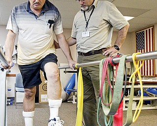 STEPPING UP: Physical therapist Kenneth Lamb helps veteran Paul Zornjack exercise at the Veterans Affairs Youngstown Outpatient Clinic. The clinic has helped more than 10,000 veterans each year since 2005 with injuries and disabilities suffered during their duty.
