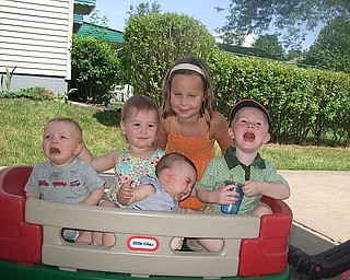 Wagon pain: From left, boys in front, Ryan Bassetti, Anthony Bassetti (tilted) and Andrew Bassetti have various reactions to sitting in a Little Tikes wagon in driveway during family visit. In back middle, from left, girls are Meredith Ashbaugh and Olivia Ashbaugh. The cousins are from Columbus, California and Pittsburgh.