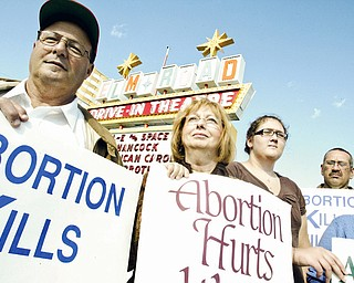 TAKING A STAND: (Left to right) Pastor Nick Furrie, of Shiloh Gospel Church in Girard, Carolyn Furrie, Savanna Frantz, 12, of Girard, up anti-abortion signs on Elm Road Northeast in Warren  during an anti-abortion demonstration Sunday.