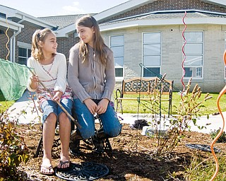 """TOGETHER TIME: (Left to right) Bailey Williamson, 9, of Youngstown, and Brooke Smith, 10, of Youngstown, play in the Paul C. Bunn Elementary's new """"Butterfly Courtyard"""" Sunday afternoon before a ribbon cutting ceremony for the new school."""