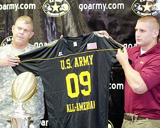 Mooney football player John Simon shows off a jersey presented to him Army Sgt  Michael Thompson. Mooney was named to all army team during a ceremony Monday at Mooney.