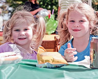 Carolyn, 4, and her sister Evelyn, 6, Engle are enjoying their food at the free Fall festival at Idaho Road Church where their father is the Pastor.