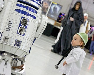 Nathaniel Slivkoff (14 months) of Niles hangs out with R2D2 at the Screaming Tiki Comic and Pop Culture Convention. Hopefully Darth Sidius (in background) doesn't get Nathaniel to join the dark side!