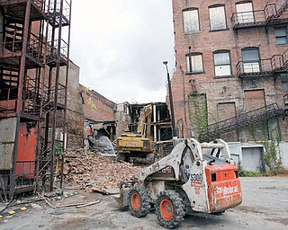 TEARING DOWN: A bulldozer is a sure sign that the 90-day remediation and demolition project of the State Theatre and the Armed Forces Building on West Federal Street has begun.  The two buildings, between the Wells Building and the John R. Davis Building, will eventually become a high-tech site.