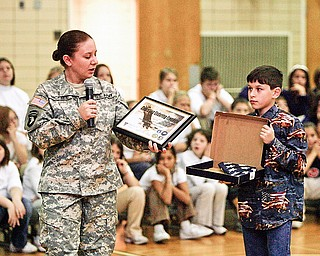 SPECIAL GIFT -  Army National Guard Specialist Sandra Nickells with her son Tyler Nickells presented a flag to the school - during the ceremony at Frank Ohl Middle School in Austintown.
