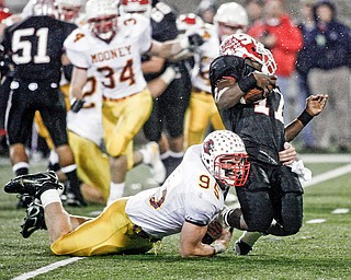 BENDING BUT NOT BREAKING - Mooney's John Simon #95 - catches Big Reds QB #17  Dwight Macon for a big loss during first half action at Fawcett Stadium in Canton