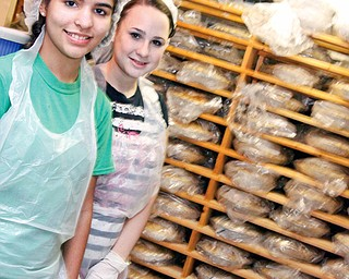 L-R Poland Seminary sophomore Janett Ziegler (15) and junior Lisa Downing (16) stand inside the freezer filled with pies they helped prepare at Angels for Animals that will be kept frozen until sold the day before Thanksgiving.