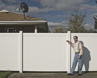 """Bill Bogan, a gay, Caucasian male, and outspoken advocate of AIDS/HIV awareness, stands near the high white fence that separates his yard from his neighbors in Struthers. Since he was diagnosed with HIV in the mid-nineties, Bill said he has come face to face with the stigma attached to the disease continually. First, when he was fired after his employer found out what his prescriptions were for and, most recently, while working in his backyard. Bill said he heard his neighbors discuss how their property values will sink as a result of his status.  """"If I move, they were saying, my house would have to be burned down,"""" Bill said."""