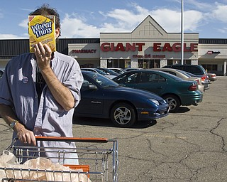 """Christian Edward Owens, a gay, white HIV+ male from Warren blocks his face with a box of Wheat Thins on his way out of a Giant Eagle Supermarket. Chris said he has moved all over the country because disclosing his status continually leaves him ostracized wherever he is living.   """"People don't know how big the HIV population is. If you look around the grocery there's someone with HIV. We eat food...we're just like you,"""" he said."""