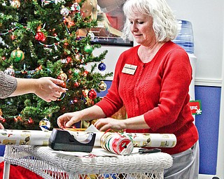 L-R Home Instead Senior Care Community service director Dawn Trickett of Cornersburg wrap a couple of donated presents to give to Senior Citizens who may not be expecting gifts