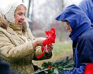 Fixing bows on the wreaths Barbara Delisio of Poland and Doris Purner both part of the Master Gardners programs affix bows to the wreaths as 27 Christmas wreaths were placed on the gravestones of 27 veterans in Zion Lutheran Cemetery  in Boardman to honor those who gave their lives while serving in the armed forces.