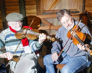 Fiddlers Dennis Kempthorne, left, of Homeworth and Frank Krygowski of Poland were among  the traditional entertainers at the Christmas at the Old Mill in Mill Creek Park Sunday. They were playing traditional Irish and American folk songs.