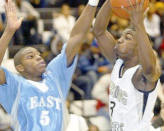 Harding's Fred Williams shoots past Mark Thornton of East during Friday game at Harding.