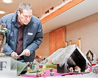 NATIVITY DISPLAY: Jim Beeman of Hiram looks at a group of Nativities at the third annual nativity Display at Villa maria Community Center in Villa Maria, Pa. The display includes 150 Nativities from all over the world from family and community collections.