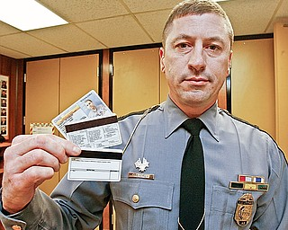 Lt. Chris Heverly of the Ohio State Highway patrol Canfield Post displays the new (bottom) and old state driver's licenses. The license underwent changes to its appearance last month to make reading the information easier for law enforcement.