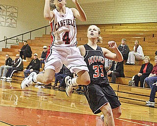 HIGH FLYING CARDINAL: Jillian Halfhill (4) drives to the bucket as North Canton Hoover's Jessica Carpenter (33) plays defense during Wednesday's game in Canfield. The Vikings tripped up the Cardinals, 48-45, with a winning layup and free throw by Allison Pearce.