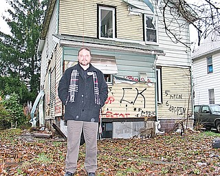 SLUM BUSTER: Warren Police Detective Patrick Marsico has focused his energy since November on charging the owners of Warren condemned homes with a criminal offense for failing to demolish or repair the homes. Marsico stands in the rear yard of a condemned home on Haymaker Avenue Northwest, a street hit hard by local housing and economic conditions. The house is missing much of its aluminum siding, has broken windows, trash and even missing cement blocks.