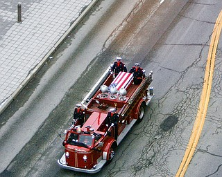 """PROCESSION: Youngstown Fire Department's 1952 parade truck carries the coffin of former Fire Chief Rocco """"Rocky"""" Russo through the downtown area and past Fire Station No. 1 on Martin Luther King Jr. Boulevard. Russo, 84, died Monday. He joined the department in 1952 and retired in 1988. He was appointed chief in 1978. His funeral was Friday at Western Reserve United Methodist Church, and several firetrucks led the procession from the Rossi and Santucci Funeral Home in Boardman to the church."""