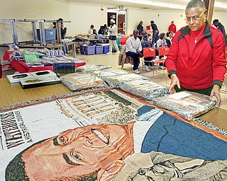 WORK OF ART: Marsha Dykes of Girard displays tapestry throws she had for sale at a Kwanzaa event at the Buckeye Elks on North Avenue in Youngstown. The event was Monday night. The merchandise featured the likeness of President-elect Barack Obama and other black American history makers.