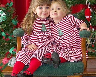 Madison Kelso (left) and Mackenzie Kelso (right) sit in Santas chair as they wait for him to tell them what they're getting for Christmas. Sent by granddad, Peter Gabriel. Mom is Lisa Kelso.