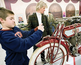 Dillwyn Damiani, age 11 of Alliance, takes a photograph of a 1913 Sears DeLuxe Invincible Twin alongside his mother Linda Damiani while viewing the Antique Motorcycle Show at the National Packard Museum in Warren. Approximately 30 bikes are on display until May 31st with models dating back to 1902 and several bikes having been made in ohio. The National Packard Museum at 1899 Mahoning Ave. in Warren is opened Tuesday-Saturday  12pm-5pm and Sunday 1pm-5pm.