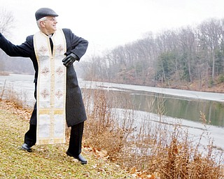 Father Daniel Rohan, of St. Marks Orthodox Church in Liberty, throws a wooden cross into Lake Glacier at Mill Creek Metro Park during The Great Blessing of Water ceremony held Tuesday afternoon.