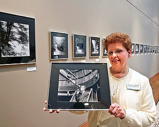 "Norma Roden, special events coordinator at Mill Creek Parks' Fellowside Riverside Gardens, shows off a photograph of Ernest Vickers, the park's first naturalist. Vickers' black-and-white photos are on display at the gardens' D.D. and Velma Davis Education and Visitor Center in ""Ernest Vickers Retrospective."" VIckers, also a botanist, took photographic images from the late-19th centuries that feature well-known park landmarks and nature scenes."