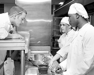 Chef Matthew Putzier overlooks the work of students Abbey Zarnick (17) of Greenford and Maurice Wallace (17) of Austintown have done for the practice cooking for MCCTC's new Oak Wood Restaurant in Canfield.