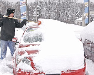 Sales and Leasing Professional Dennis Sima scrapes snow off of a Red Chevy Cobalt at Greenwood Chevrolet, Saturday January 10, 2009