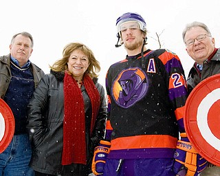 "TAKING AIM: Hank Conrad, Poland Rotary president, left; Mary Ann Martinko, chairwoman of Poland Rotary's Chili Open Auction; Carl Nielsen, who plays defense for the Mahoning Valley Phantoms; and Larry Warren, Poland Rotary member, brave the cold while they gear up for Saturday's Chili Open, a ""golf"" tournament where participants try to hit hockey pucks into a goal manned by a Phantoms player."