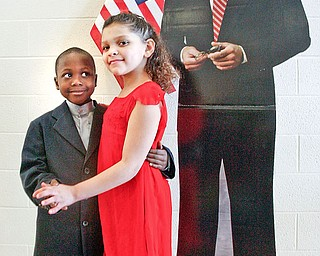 DANCING WITH A STAR: Naelemn Hasley, 6, left, and Alicia MOore, 7, pose in front of a cardboard cutout of President Barack Obama. They were selected to represent the presidenta dn first lady at an inaugural ball Wednesday at Paul C. Bunn Elementary School