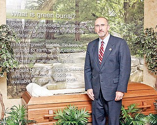 Joseph Lane, president and chief operating officer of Lane Funeral Homes, stands with a green burial display that offers clients an explanation of a more natural and environmentally friendly form of burial. Green burial is defined as a body's returning to the earth naturally, without embalming fluid and with biodegradable materials.