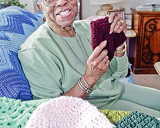 Lillie Smith of Youngstown with some of the crocheted hats she has made for chemo patients.