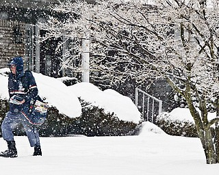 US Postal Service letter carrier John Poprik, who has been delivering mail for 21 years, trudges through Wednesday's snowfall along Leyton on Youngstown's Westside.