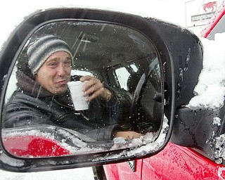 Snowplow driver Carl Dohar of Arrow Asphalt takes a break with a cup of coffee while plowing