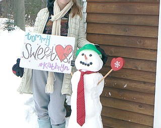 Kathryn Mason, a junior at Canfield High School, delivers a snowman invite to senior Tommy Johnson for the Sweethearts Dance on Feb. 21.