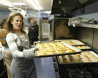 Rachelle Miller pulls hot cookies out of the oven as the church makes Hamentaschen cookies for Purim- robertkyosay