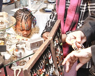 Janiyah Diggs (4) and her older sister Zariyah (12) of Warren inspects African cultural jewelry at YSU's African Marketplace for Black History Month in the Chestnut room at Kilcawley Center, Saturday February 7, 2009