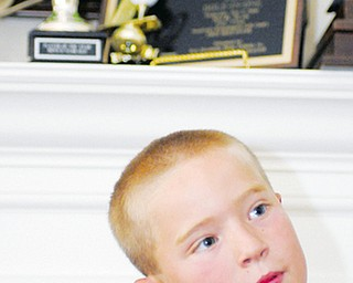 Brian Terlesky, 8, of Boardman stands in front of some of his trophies in his home. Brian dreams of playing in a PGA tournament one day.