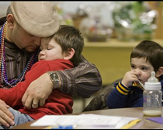 2.24.2009 Miguel Cuevas and his son Jayden, 3, both residents of Lowelville, pray, while Rocco, 1, explores the possibilities of what beads can be used for during a Mardi Gras celebration at Faith Community Church on Midlothian Ave in Youngstown, Ohio Feb. 24, 2009. Geoffrey Hauschild