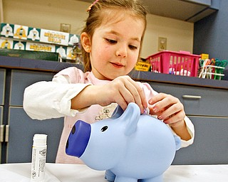A penny saved is a penny earned as Natalie Tobey 3,  puts money in the bank she received from the program - at the Librarys Smart Money program that was presented at Boardman Library by John Yingling