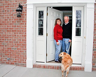Dick and Sharon Wade with their dog R.T. on the front porch of their rebuilt home in Poland. The Wade's had a tree of their own that caused their home to be demolished.