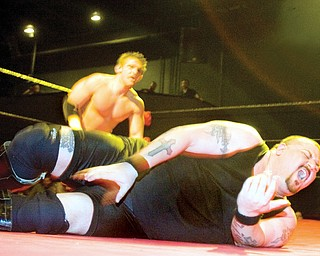 """John Cathelin known as """"The Bouncer,"""" of Broadview Heights, writhes in pain on the mat while wrestling Nicky Valentino known as """"The Pinnacle"""" during a match at The Wedge Nightclub in Autintown, on Friday evening. Catheline, who has been wrestling for 13 years, won the fight against Valentino who has just been wrestling for a couple months. """"Ever since I was four years old, this was the only thing i wanted to do,"""" said Catheline."""