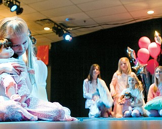 Hannah holds her bitty baby twin close while modeling sleepwear on stage during the American Doll fashion show at Mr. Anthony's Banquet Center on South Avenue in Boardman.